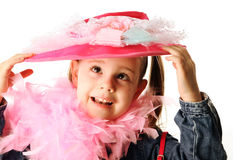 Funny preschool girl playing dress up. Portrait of an adorable preschool girl playing dress up with a fancy hat, purse, and pearl necklace isolated on white Royalty Free Stock Images