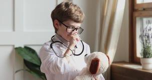 Funny preschooler boy wear medical coat hold stethoscope listen toy