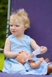 Funny preschooler girl feeding doll Stock Image
