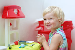 Funny preschooler girl plays with toy kitchen Royalty Free Stock Photo
