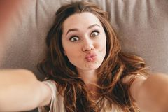 Funny pretty lady lies on sofa indoors make selfie. Photo of young amazing funny pretty lady lies on sofa indoors. Looking camera make selfie royalty free stock photos
