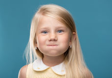 Funny, pretty young girl. Funny, cute, young girl inflated cheeks, on a blue background Royalty Free Stock Photography
