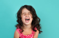 Funny, pretty young girl. Portrait of a happy, positive, smiling, little girl, cyan background Royalty Free Stock Photo