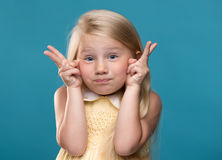 Funny, pretty young girl. Funny, pretty, young girl showing four fingers on a blue background Stock Photo