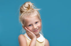 Funny, pretty young girl. Smiling, on blue background Royalty Free Stock Image