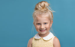 Funny, pretty young girl smiling. On blue background Royalty Free Stock Photo