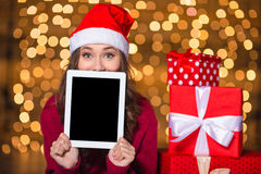 Funny pretty young woman hiding behind tablet blank screen Royalty Free Stock Photo