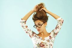 Funny pretty young woman in round glasses holding her hair up ov. Funny pretty young woman in round glasses holding her hair up Royalty Free Stock Image