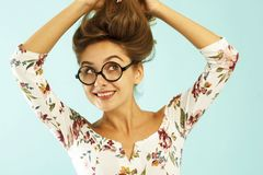 Funny pretty young woman in round glasses holding her hair up. Over blue background Stock Photography
