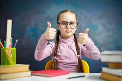 Funny Primary Schoolgirl Thumb Up Photo Portrait. Pretty Smart Student Girl in Glasses Hold Little Fist for Mood Expression. Nice Caucasian Child Long Braid royalty free stock image