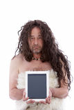 Funny primitive man holding a PC tablet. Funny long haired primitive man holding a PC tablet, portrait on white background Royalty Free Stock Photos
