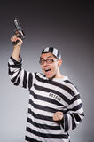 Funny prisoner with firearm on gray. The funny prisoner with firearm on gray royalty free stock image