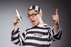Funny prisoner with firearm isolated on gray Royalty Free Stock Image