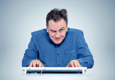 Funny programmer man with keyboard in front of computer Stock Photography