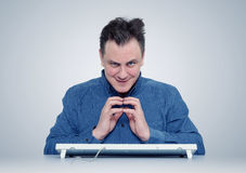 Funny programmer man with keyboard in front of computer Royalty Free Stock Image