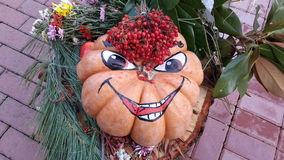 Funny pumpkin with smile. Funny painted pumpkin with berry, leaves and flowers, Halloween in city park Royalty Free Stock Photography