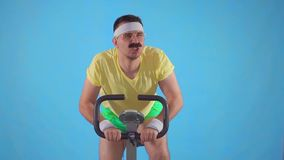 Funny purposeful man athlete of the 80`s with a mustache on exercise bike on a blue background slow mo. Funny purposeful young man athlete of the 80`s with a stock video footage