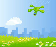 Funny quadrocopter flying over green field. City on the background Royalty Free Stock Image