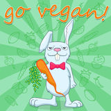 Funny rabbit with a carrot encourages vegetarianism Royalty Free Stock Image