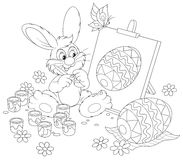 Easter Bunny artist. Funny rabbit drawing a decorated Easter egg to the upcoming holiday, black and white outline illustration for a coloring book Stock Image