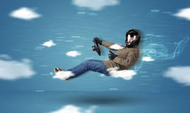 Funny racedriver young man driving between clouds concept Stock Photo