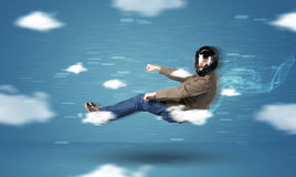Funny racedriver young man driving between clouds concept Stock Images