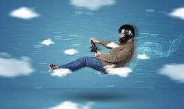 Funny racedriver young man driving between clouds concept Stock Image