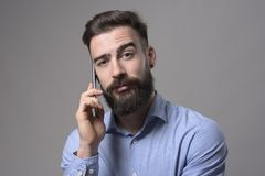 Funny raised eyebrow puzzled facial expression of young business man talking on the phone looking at camera. Over gray background Stock Photography