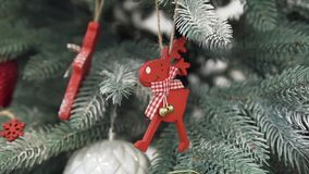 Close up of the christmas tree decorated with silver pine cones and red deer toys. Funny red deer toy decorates the christmas tree with silver shade stock footage