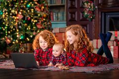 Free Funny Red-haired Children Next To Christmas Tree And Gifts Communicate Online Through A Laptop Stock Photo - 200637330