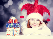 Funny red-haired girl in christmas cap with gift boxes. Royalty Free Stock Photography