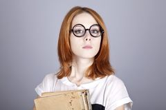 Funny red-haired girl with old book. Stock Photos