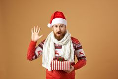 Funny red-haired man with beard dressed in a red and white sweater with deer, white knitted scarf and a hat of Santa royalty free stock image
