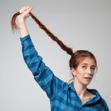 Funny red haired model girl with long braid hair. She holds long braid up. Stock Image