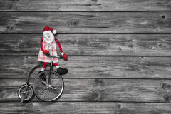 Funny red santa claus on wooden grey background in hurry for buy. Ing christmas presents sitting on a old bike Royalty Free Stock Photo