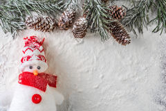 Funny red and white snowman. Red and white snowman and a snowy fir branch with pine cones on a snow background Royalty Free Stock Image