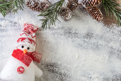Funny red and white snowman. Red and white snowman and a snowy fir branch with pine cones on a snow background Royalty Free Stock Photos