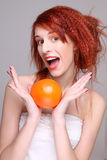 Funny redhaired woman with orange in her hands. Over grey Royalty Free Stock Photos