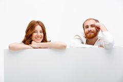 Funny redhead boy and girl hiding at white table Royalty Free Stock Image