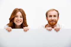 Funny redhead boy and girl hiding at white table Royalty Free Stock Photo