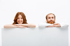 Funny redhead boy and girl hiding at white table Stock Image