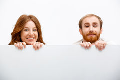 Funny redhead boy and girl hiding at white table Stock Photography