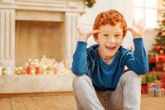 Funny redhead boy making faces while sitting on floor. No time for worries. Extremely happy kid getting excited and grinning broadly into the camera while making Royalty Free Stock Photo