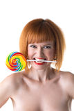 Funny redhead woman squeezes lollipop by teeth Stock Images