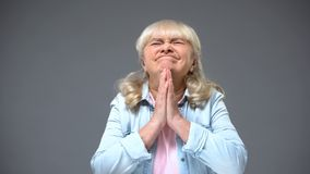 Funny retiree lady making wish expecting good news, waiting children for holiday stock photography