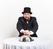 Funny retro gentleman holding a silver cloche Stock Photography