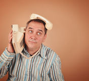 Funny Retro Phone Man. A retro 1970's man is using an old telephone in an unusual funny way on an isolated background for a communication or technology concept Royalty Free Stock Image