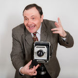 Funny Retro Photographer. Photographer with a large format vintage camera taking photo in a studio Stock Photo