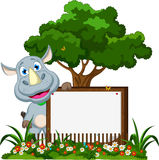 Funny rhino cartoon with blank sign on garden Royalty Free Stock Image