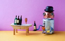 Funny robot alcoholic gets drunk. Wine party event concept. Creative design copper head long nose cyborg with wine glass. And bottle. Wooden table, bucket with Stock Photo